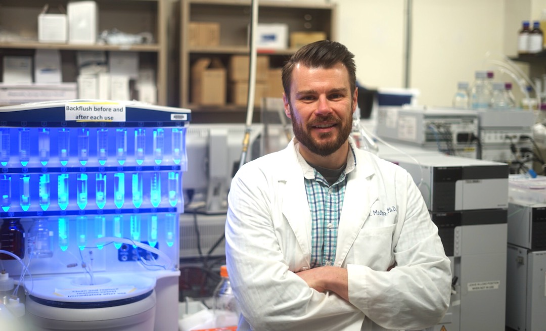 Scott Medina in his lab in white lab coat, arms crossed
