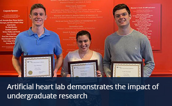 Three students holding their undergraduate research awards on an orange background