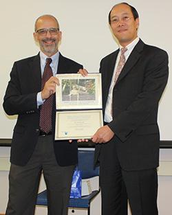 Arthur Motta, nuclear program chair, presenting a certificate to Zhong He (right).