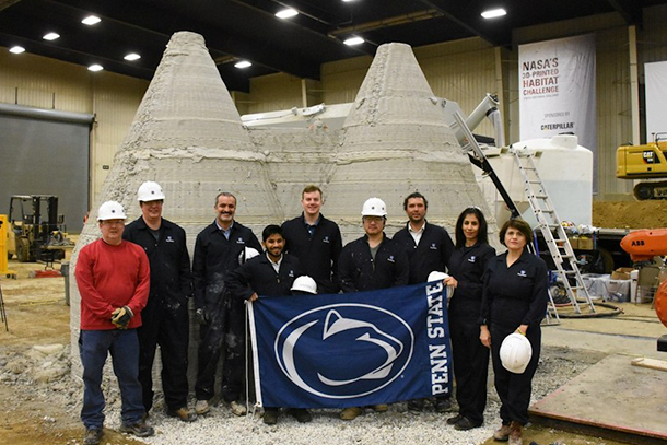 Members of the Penn State team pose in front of the first fully enclosed 3D-printed housing structure